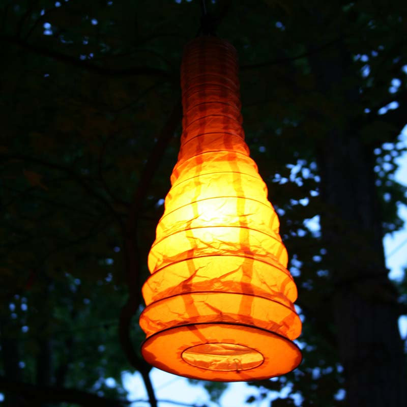A yellow paper Chinese lantern hanging in a park.
