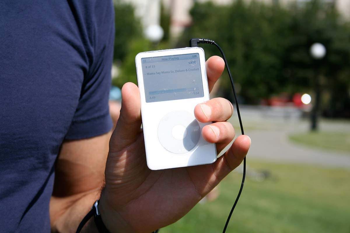 An iPod held by a man in the park.